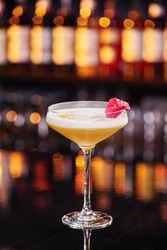 Elegant female yellow cocktail with white foam, decorated with pink flower petal on dark table against the background of blurred bar with expensive alcohol. Close-up. Space for inscriptions