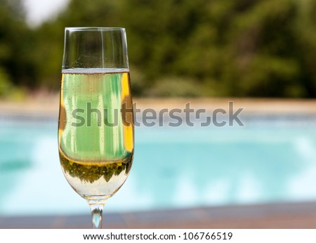 Elegant flute glass of sparkling white wine or champagne by side of swimming pool