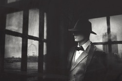 elegant gangster man behind window looking at the city