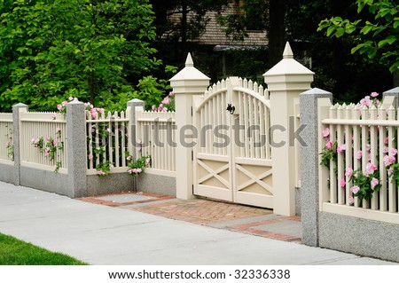 Elegant gate and fence of residential house. Wood, granite, brick; rose bushes coming out through picket posts