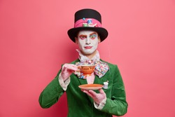 Elegant gentleman with makeup dressed in masquerade costume poses with tea cup against rosy studio wall. Serious mad hatter celebrates halloween party. Wonderland character drinks hot beverage
