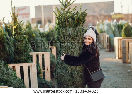 Elegant girl buys a Christmas tree. Woman in a fur coat. Beautiful lady with dark hair.