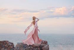 elegant girl elf blond fair wavy hair  tiara. long light pink fluttering fly dress standing high tower old castle. feel free blue sea pastel art. beach coast relax. fantasy mysterious woman silhouette