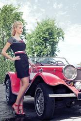 Elegant girl poses near the red car. Cabriolet jaguar.