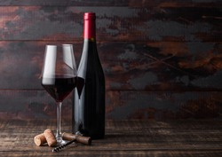 Elegant glass and bottle of red wine with corks and corkscrew on dark wooden background.