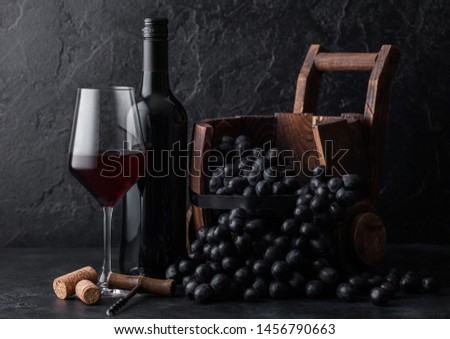 Elegant glass and bottle of red wine with dark grapes inside vintage wooden barrel on black stone background. Corks and corkscrew on board #1456790663
