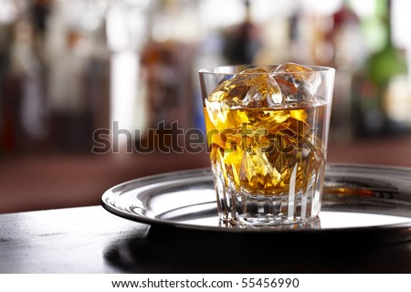 Elegant glass of scotch whiskey sitting on silver tray, shot in bar with space for copy