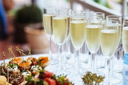 Elegant glasses with chilled champagne stand in row next to canapes and snacks on picturesque background. Party and holiday away. Picnic.