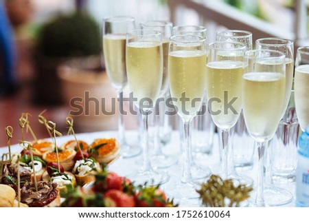Elegant glasses with chilled champagne stand in row next to canapes and snacks on picturesque background. Party and holiday away. Picnic. Photo stock ©