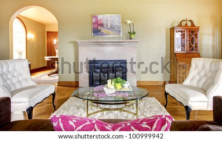Elegant gold and pink fireplace in living room interior with white chairs.