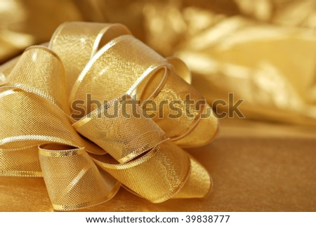 Elegant gold gift bow with shiny wrapping paper in background.  Macro with extremely shallow dof.
