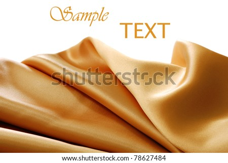 Elegant gold satin on white background with copy space. Macro with shallow dof.