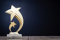 Elegant gold winners trophy with shooting stars to be awarded for the first place in a competition or championship over a dark blue background with copy space