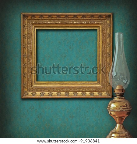 Elegant golden empty frame on rich Victorian damask texture and an antique brass oil lamp