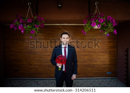elegant gorgeous groom with red tie posing with red bouquet at the background of brown wall