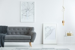 Elegant, gray sofa with wooden legs and large map posters on a white wall in a designer minimalist living room interior of an architect