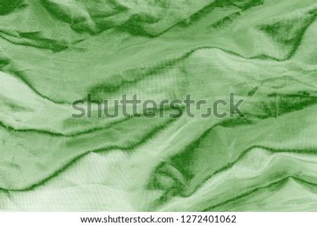 Elegant green textile background. Silk cloth texture. Fabric pattern.