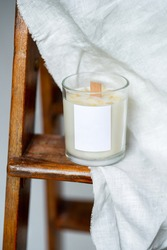 Elegant home decoration with wooden wick burning candle from soy wax with label space on a background of white linen fabric