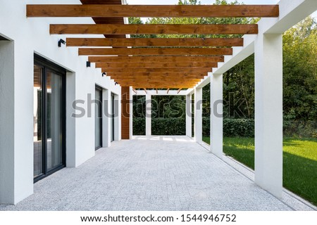 Elegant home patio with stone floor and wooden elements on ceiling and green grass backyard Foto d'archivio ©