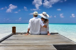 Elegant honeymoon traveler couple hugging on a wooden jetty and enjoy their tropical holiday in the Maldives islands