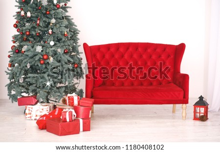 Elegant Interior with red sofa decorated for celebrating New Year. Comfort home in Christmas Holidays