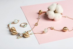 Elegant jewelry and cotton flower on color background