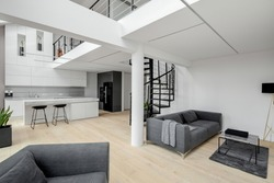 Elegant kitchen and contemporary living room in white apartment with mezzanine and stylish black stairs