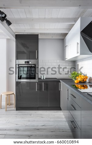 Elegant kitchen interior with brick wall, gray furniture and wooden floor