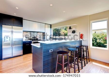 Elegant kitchen room with black wood storage combination with stoned backsplash and decorative vase and wall shelf