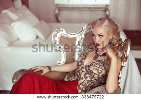Elegant lady. Fashion beautiful sensual blond woman with makeup in luxurious prom dress with bijou, posing on modern armchair with sliver frames. #338475722