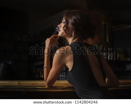 elegant lady in a black dress, in a restaurant at a bar counter alone