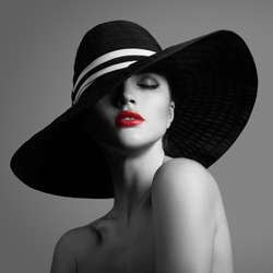 Elegant lady in hat. Black and white fashion portrait. Red lips.