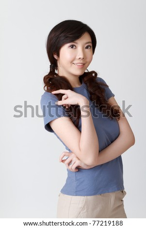 Elegant lady of Asian, half length closeup portrait on grey studio background.