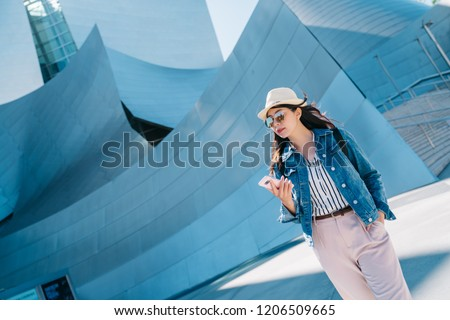 elegant lady walking around Walt Disney concert hall with cellphone in her hand. popular sightseeing spot to visit in Los Angeles. young tourist using online tour guide on smartphone.