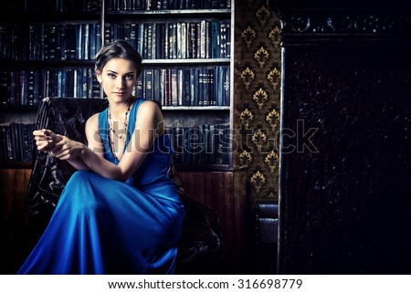 Elegant lady wearing evening dress sitting in the chair in the old vintage library. Beauty, fashion.