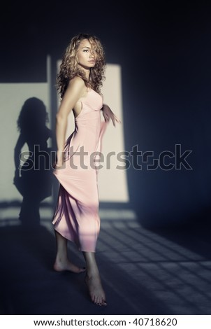 Stock Photo Elegant lady with curly hairs dancing indoors with shadow