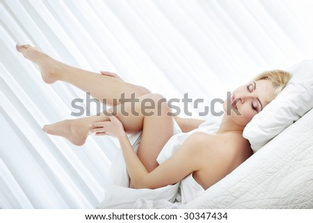 Elegant lady with naked legs laying on the bed at the morning