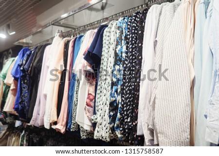 Elegant light blouses hanging on metal rack in modern clothes shop