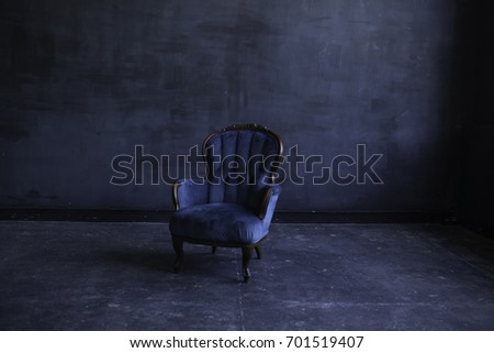 Elegant living room in blue tones. Blue Velor armchair. Vintage designer chair on dark background. Texture chair. Classical style