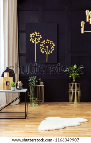 Elegant living room interior with golden accents, painting on a black wall, plants and fur rug. Real photo