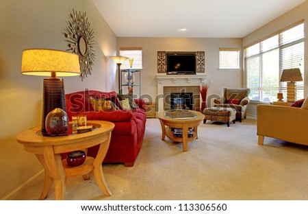 Elegant living room with red sofa, fireplace, TV and many windows.
