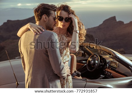 Elegant lovers posing next to the convertible car