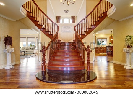 Elegant luxury double staircase with deep stained wood railing.