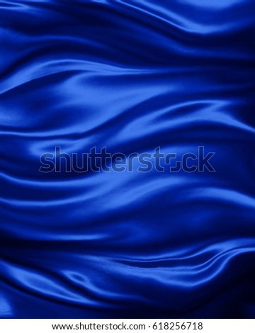 elegant luxury sapphire blue background with wavy draped folds of cloth, smooth silk texture with wrinkles and creases in flowing fabric