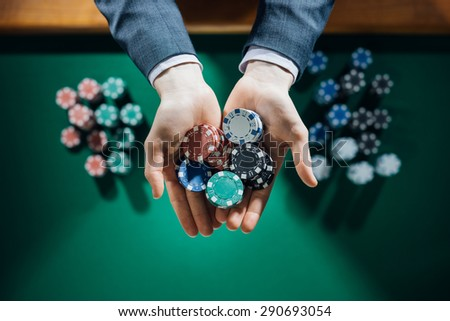 Elegant male casino player holding a handful of chips with green table on background, hands close up top view