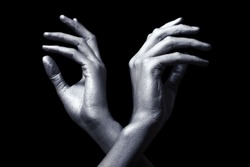 elegant male hands in silver paint isolated on black background
