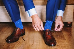 Elegant man dresses shoes. Two men's hands tie shoelaces. The man is wearing brown leather shoes, a blue suit and stylish socks. Men's fashion. Wedding fashion.
