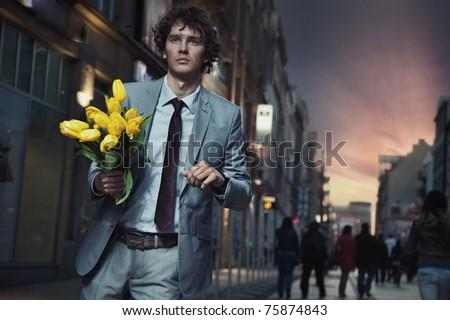 Elegant man holding flowers - stock photo