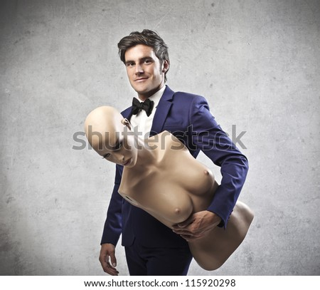 Elegant man holding the torso of a dummy
