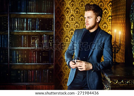 Elegant man in a suit with glass of beverage stands in vintage room. Fashion.